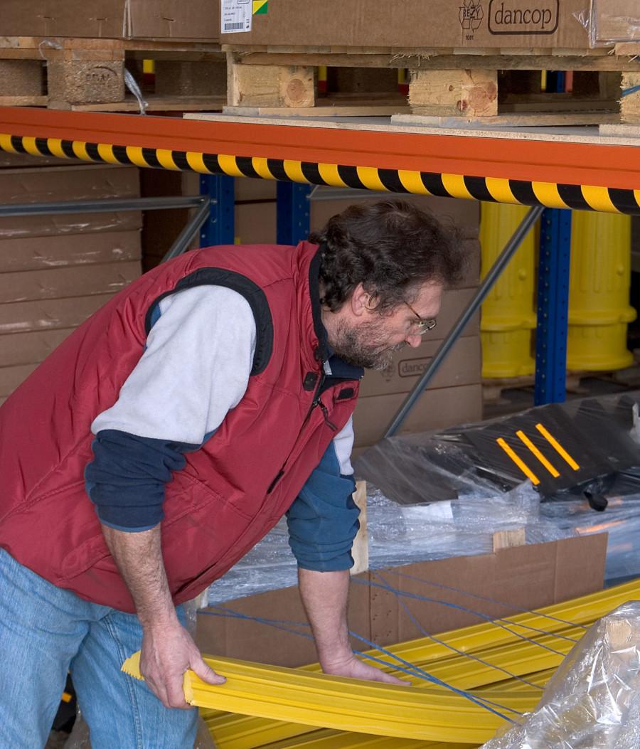 Profil ochronny, elastyczny typu A naklejony na stalowy trawers regału paletowego, chroniący głowę pracownika pobierającego przedmioty z poziomu 0